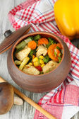 Baked mixed vegetable with chicken breast in pot, on wooden background — Stock Photo