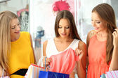 Three beautiful young woman in shop with shopping bags — Stock fotografie
