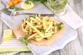 French fries on tracing paper on board on napkin wooden table — Stock Photo
