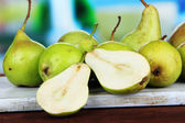 Pears on wooden cutting board, on bright background — Stock Photo