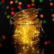 Christmas lights in glass bottle on blur lights background — Stock Photo #31021299