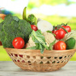 Fresh vegetables in basket on wooden table on natural background — Stock Photo
