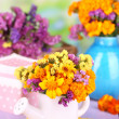 Stock Photo: Bouquet of marigold flowers in watering con wooden table on natural background