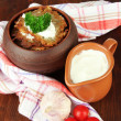 Potato pancakes in pot, on wooden background — Stock Photo