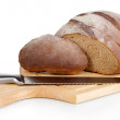 Stock Photo: Cut bread on wooden board isolated on white