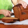Stock Photo: Cutting bread on wooden board on wooden table on natural background