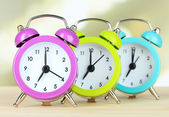 Colorful alarm clocks on table on light background — ストック写真