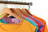 木製ハンガー棚の背景上にカジュアルな t シャツ各種 — ストック写真
