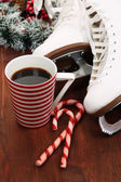 Figure skates with cup of coffee on table close-up — Foto Stock