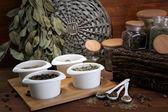 Assortiment d'épices en cuillères blanches et bols, sur fond de bois — Photo
