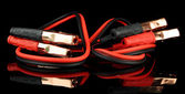 Car battery jumper cables on black background — Stock Photo