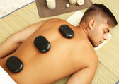 Young man relaxing with hot stones on back before massage — Stock Photo