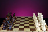 Chess board with chess pieces on dark color background — Stok fotoğraf