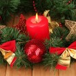 Christmas composition with candle and decorations in red and gold colors on wooden background — ストック写真