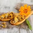 Fresh and dried calendula flowers on wooden background — Stock Photo #31106885
