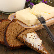 Butter on wooden holder surrounded by bread and milk on wooden table close-up — Stock Photo #31107189