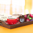 Cup of tea with cakes on wooden tray on table in room — Stock Photo #31109411