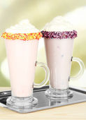 Delicious milk shakes on table on light background — Stock Photo