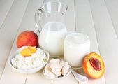 Fresh dairy products with peaches on wooden table close-up — Stock Photo