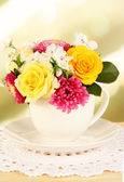 Beautiful bouquet of bright flowers in color mug, on wooden table, on bright background — Stock Photo