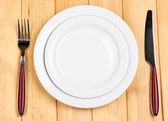 Knife, color plate and fork, on wooden background — Stock Photo