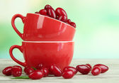 Fresh cornel berries in red cups on wooden table — Stock Photo