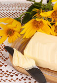 Butter on wooden holder surrounded by flowers close-up — Stock Photo