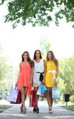 Three beautiful young woman with shopping bags in park — Zdjęcie stockowe