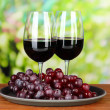 Ripe grapes and glasses of wine, on bright background — Stock Photo