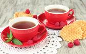 Tazas de té con galletas y frambuesas en primer plano de la mesa — Foto de Stock
