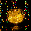 Christmas lights in glass bowl on blur lights background — Stock Photo