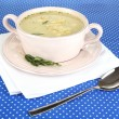 Nourishing soup in pink pan on blue tablecloth close-up — Stock Photo