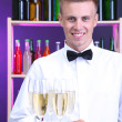 Bartender holding tray with champagne glasses — Stock Photo