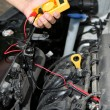 Auto mechanic uses multimeter voltmeter to check voltage level in car battery — Stock Photo #31124415
