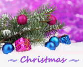 Christmas ball and toy with green tree in the snow on purple background — Stock Photo