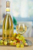 Vin blanc en verre avec la bouteille sur le plateau sur le fond de la salle — Photo