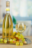 White wine in glass with bottle on salver on room background — Stock Photo