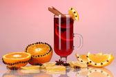 ароматный глинтвейн в стакан с пряностями и апельсины вокруг на красном фоне — Стоковое фото