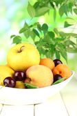 Bright summer fruits in plate on wooden table on natural background — Stock Photo