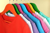 Different shirts on colorful hangers on beige background — Stock Photo