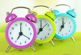 Colorido despertadores en mesa sobre fondo claro — Foto de Stock