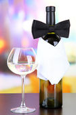 Black bow tie on wine bottle on bright background — Stock Photo