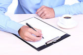 Businessman writing on document in office close-up — Stock Photo