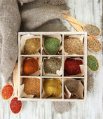 Assortment of spices in wooden spoons and box, on wooden background — Stock Photo