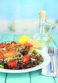 Boiled crab on white plate with salad leaves and tomatoes,on wooden table, on bright background — Stock Photo