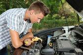 Ung förare reparera bilen motorn utomhus — Stockfoto