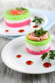 Colored rice on plates on napkin on wooden table — Stock Photo