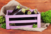 Fresh eggplants in wooden box on table on wooden background — Stock Photo