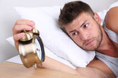 Handsome young man in bed — Stockfoto