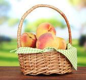 Pêssegos maduros de doce na cesta de vime, no fundo brilhante — Foto Stock